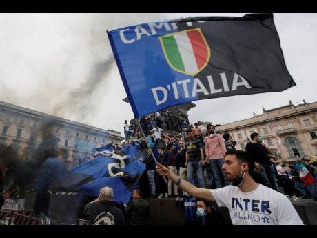 Inter Milan fans celebrate and shout slogans in Piazza Duomo square in front of the gothic cathedral after Inter Milan won its first Serie A title in more than a decade after second-placed Atalanta drew 1-1 at Sassuolo, in Milan, Italy, Sunday, May 2, 2021.