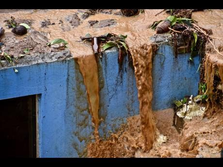Water flows over the roof of a home after heavy rains poured down, causing flooding and mudslides that damaged some homes and further battered areas already burdened by heavy ashfall from eruptions of La Soufriere volcano, in Kingstown, on the Caribbean island of St Vincent and the Grenadines last Thursday.