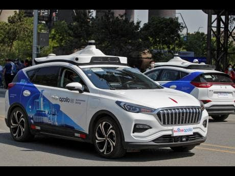 Baidu Apollo Robotaxis move on a street at the Shougang Park in Beijing yesterday.