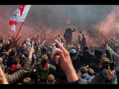 Ajax supporters celebrate outside the syadium as their team scored their second goal in the Dutch Eredivisie Premier League title during the match against  Emmen at the Johan Cruyff Arena in Amsterdam, Netherlands,  yesterday.
