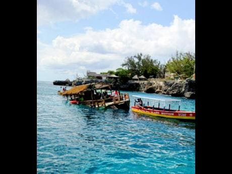 The thatched 'party boat' (left) that capsized off the Negril coastline on the weekend.