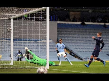Manchester City's Riyad Mahrez (centre) scores his side's second goal of the game against Paris Saint-Germain during the Champions League semifinal second-leg match at the Etihad Stadium, Manchester, England, yesterday.
