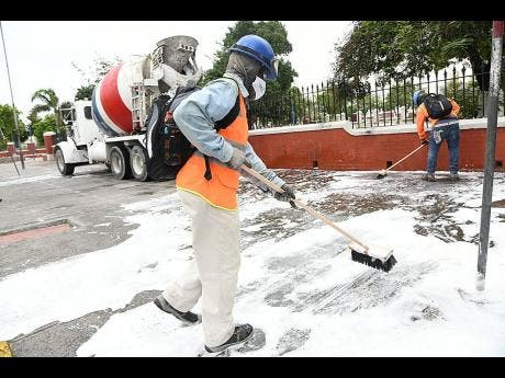 Workmen employed to Carib Cement Company and Pre-Mix Limited scrub the sidewalk around the St William Grant Park in downtown Kingston last Labour Day.