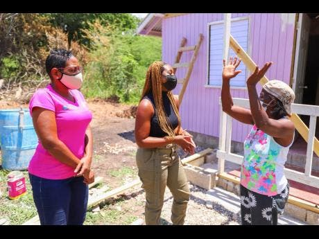 Lelieth Fraser (right) explains how she became a victim to fire in December 2019. Fraser was the beneficiary of a two-bedroom house sponsored by BOOM Energy Drink under Food For The Poor's 'Tan Ah Yuh Yard' COVID-19 campaign. Looking on are Marsha Burrell-Rose (left), Food For The Poor's development and marketing manager, and attorney-at-law Lecia-Gaye Taylor, who was a victim to fire as a child.