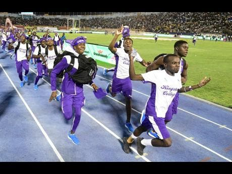 Kingston College track team celebrate their 2019 Champs win.