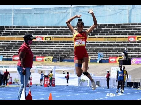 Wolmer's High School's Natrilia Campbell launches herself into the sandpit during the Class Four Girls long jump event at the ISSA/GraceKennedy Boys and Girls' Athletics Championships at the National Stadium yesterday.