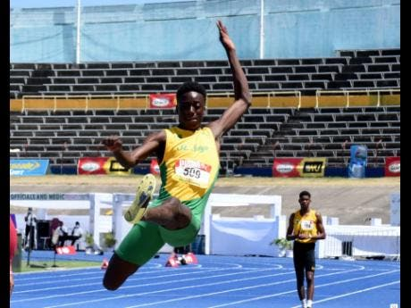 St Jago High School's Balvin Israel in action in the Class Two Boys long jump yesterday.