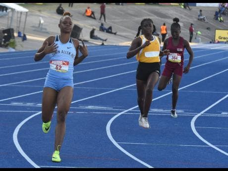 Edwin Allen's Tia Clayton (left) wins her heat in the Class Two Girls 100m sprint at the ISSA/GraceKennedy Boys and Girls' Athletics Championships at the National Stadium yesterday.