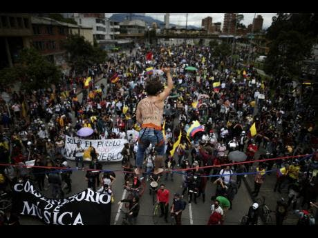 A tight rope artist stands over demonstrators as they march during an anti-government protest in Bogota, Colombia, last Wednesday. Colombians have taken to the streets for weeks across the country after the government proposed tax increases on public services, fuel, wages and pensions, but have continued even after President Ivan Duque walked back the tax hike.