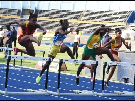 Tiana Marshall (left) from Wolmer's Girls on her way to winning the Class 4 Girls' 70 metres Hurdles at the ISSA/GraceKennedy Boys and Girls' Athletics Championships ahead of Tihanna Reid (second left) - Hydel, Kecia King (second right) - Vere Technical; and another Wolmerian, Natrilia Campbell.