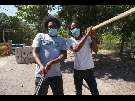 Entertainer Rawpa Crawpa (left) and Khacy 'Official Boss' Mohammed move around hardware material to the site of the new house.