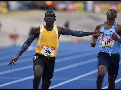 Antonio Watson from Petersfield High School (left) celebrates after winning the Class One boys 200m final at the ISSA/GraceKennedy Boys and Girls' Athletics Championships at the National Stadium on Saturday, May 15, 2021.