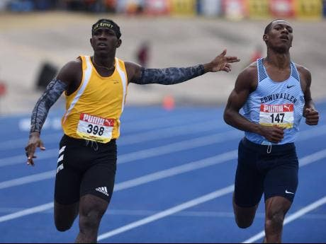 Petersfield High School's Antonio Watson (left) celebrates with a gun play gesture towards Edwin Allen High School's Bryan Levell as he crosses the finish line ahead of him in the Class One 200m final during the ISSA/GraceKennedy Boys and Girls' Athletic Championships at the National Stadium on Saturday.