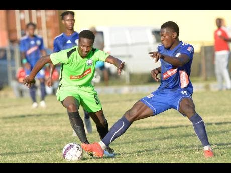 Mount Pleasant's Kevaughn Isaacs (right) gets a toe to the ball ahead of Molynes' Tyrique Wilson during a Red Stripe Premier League match at the Constant Spring Sports Complex last December.