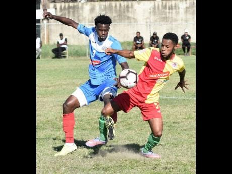 Courtney Hill (right) of Humble Lion tries to win the ball from Portmore United's Chavany Willis during their Jamaica Premier League match at the Spanish Town Prison Oval on Sunday, January 5, 2020.
