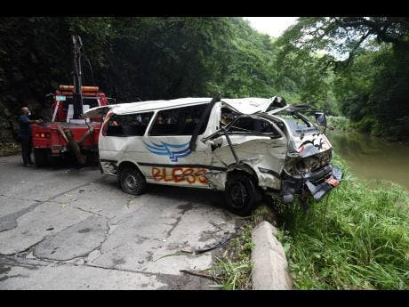 A wrecker lifts the minibus from the Rio Cobre after it was involved in an accident with a motor car along the Bog Walk Gorge yesterday in St Catherine.