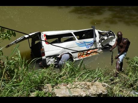 Divers attempt to attach cables to the ill-fated mini bus in order for the wrecker to lift it from the Rio Cobre.