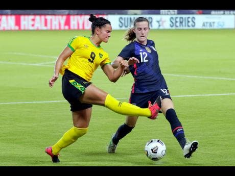 Jamaica forward Kayla McCoy (9) kicks the ball away from US defender Tierna Davidson (12) during the second half of their 2021 Summer Series on Sunday in Houston. The Americans won 4-0.