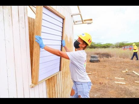 Bad Gyal Ce'Cile installs a window in a house that was constructed for Cislyn Williams in Portland Cottage, Clarendon, on Tuesday.