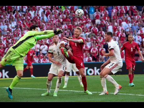 Belgium's goalkeeper Thibaut Courtois (left) punches the ball away during the Euro 2020 championship group B match between Denmark and Belgium at Parken stadium in Copenhagen, Denmark, yesterday. Belgium won 2-1.