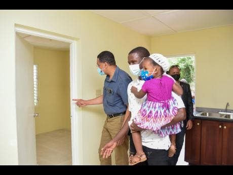 Prime Minister Andrew Holness (left), tours a new three-bedroom house in Ulster Spring with beneficiary Tristan Turner and his baby daughter Imani.  The unit was one of three handed over to families in South Trelawny last Friday under the New Social Housing Programme.