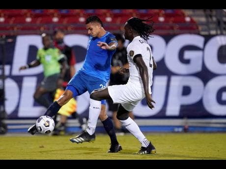 Guatemala midfielder Jorge Aparicio (left) takes a shot at goal as Trinidad and Tobago defender Aubrey David defends in the first half of a CONCACAF Gold Cup Group A match on Sunday.