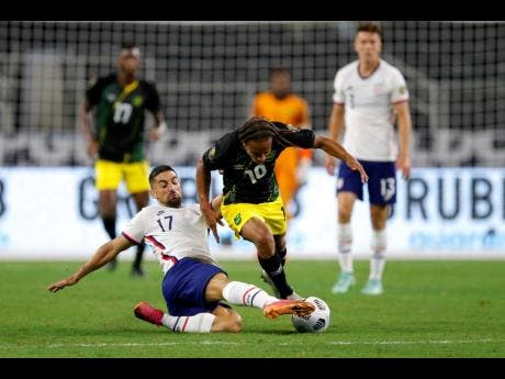 United States midfielder Sebastian Lletget (17) clears the ball away from Jamaica's Bobby Reid during the first half of last night's Concacaf Gold Cup quarter-final match in Arlington, Texas.