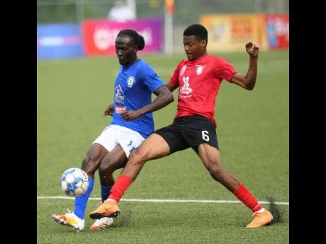 Mount Pleasant's Kesslon  Hall (left)  under pressure from Luca Kung of Arnett Gardens  during yesterday's Jamaica Premier League match at the UWI/Captain Horace Burrell Centre of Excellence.