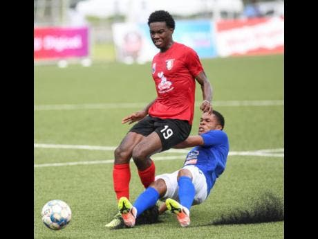 Arnett Gardens player Luca King (left) is on the end of a sliding tackle from Mount Pleasant's Sue-Lae McAlla during Sunday's Jamaica Premier League match at the UWI/Captain Horace Burrell Centre of Excellence.