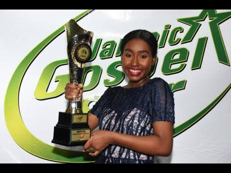 Lumsden beams as she holds the Jamaica Cultural Development Commission Gospel Star competition winner's trophy.