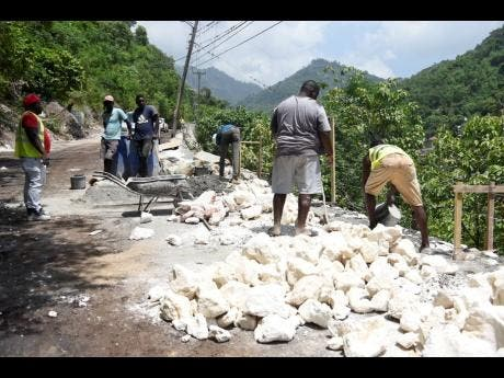 Workmen trying to complete the rehabilitation of this section of the Gordon Town main road.