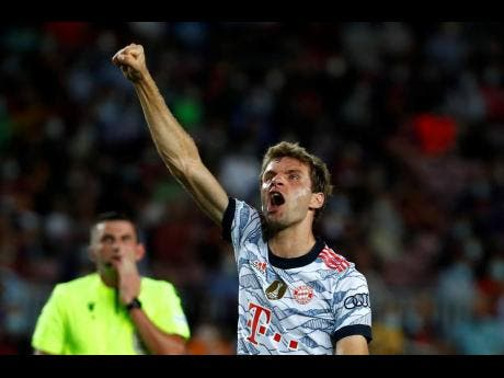Bayern's Thomas Mueller celebrates after scoring the opening goal during the Champions League Group E match against Barcelona at Camp Nou stadium in Barcelona, Spain, yesterday.