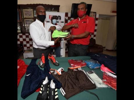 Ian Allen Wayne Shaw (right), president of  the Kingston and St Andrew Football Association, collecting football gear from Rudi Page, CEO of Enhanced Leadership Insights. The football gear was donated by English Premier League club Brentford FC.  The presentation took place at the Scotiabank Sports Club in Liguanea, St Andrew yesterday.
