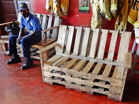 A firefighter at the Ocho Rios Fire Station sits on one of several benches that have been made by the firemen.