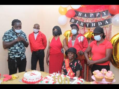 Miriam Pusey is surrounded by family members (from left) grandsons Joel 'Blingers' Pusey and Aston Burnett, and three of her five children, Patricia, Glenroy and Abeva Pusey.