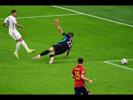France's Kylian Mbappe (left) scores the winning goal past Spain's goalkeeper Unai Simon  during the UEFA Nations League final at the San Siro stadium, in Milan, Italy, yesterday.