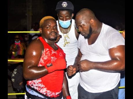 Main organiser, Young Wild Apache (centre), of the charity boxing spectacle, takes a photo with heavyweight boxers Dwayne Smith (right) and Ryan Gordon during the second bout in a charity boxing clash dubbed 'Jump Out, Thump Out' in Cockburn Gardens recently.