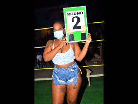 Below: This lady introduces the next round during a charity boxing clash dubbed 'Jump Out, Thump Out' in Cockburn Gardens recently.