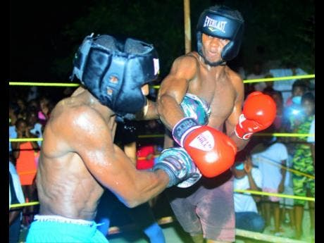 Left: Oraldo 'Jubba' Stephenson (left) of Mandella Terrace and Miracle Rhakeam from Cockburn Gardens battle in the ring during a charity boxing clash dubbed 'Jump Out, Thump Out, in Cockburn Gardens recently. Miracle won the bout.