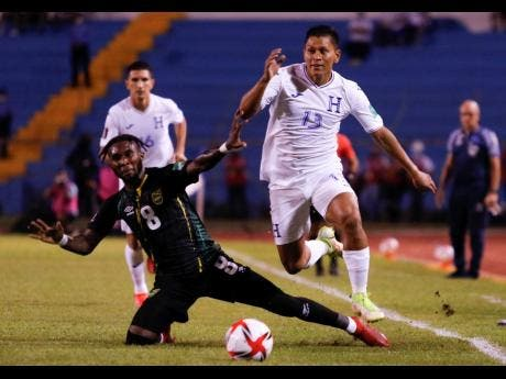 Jamaica's Oniel Fisher (left) and Honduras' Bryan Moya compete for the ball during a qualifying soccer match for the FIFA World Cup Qatar 2022 at the Metropolitan Olympic stadium in San Pedro Sula, Honduras, last night. Fisher scored Jamaica's second goal in their 2-0 win.