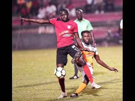Arnette Gardens player Fabian Reid (left) moves away from Dunbeholden's Clayton Pusey, in their  Red Stripe Premier League encounter at the Anthony Spaulding Sports Complex on Monday, December 24, 2018. (File)